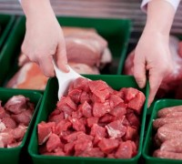 Fresh beef for goulash on display in a container at the butchery with an assistant serving a customer with a scoop